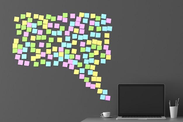 Messaggio dal messaggero dagli adesivi incollati sul muro con un laptop in piedi accanto
