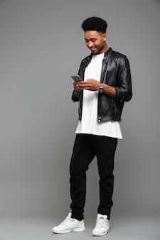 Messaggio di battitura a macchina dell'uomo afroamericano attraente felice sullo smartphone