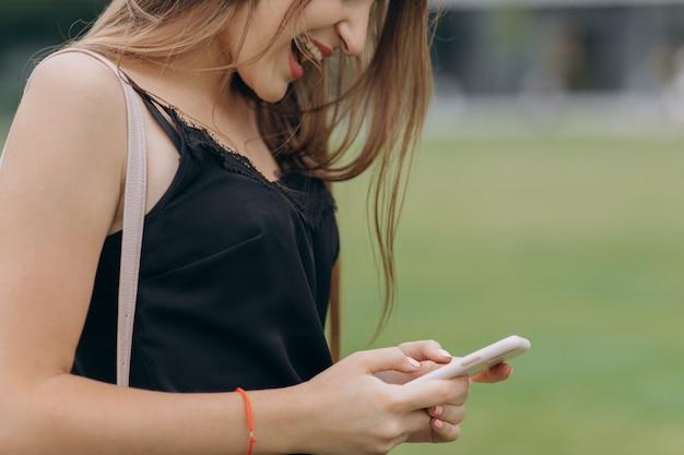Messaggio di battitura a mano della donna sullo smartphone dello schermo. chiuda sulle mani femminili che tengono lo smartphone e che visitano il sito web. studentessa che studia e che manda un sms con il telefono cellulare a casa