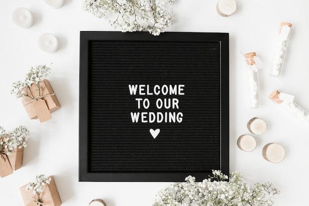 Messaggio di benvenuto su cornice nera circondato da scatole regalo; provette di marshmallow; candele e fiori su sfondo bianco