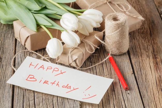 Messaggio di buon compleanno con fiori sul tavolo rustico con fiori