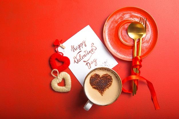 Messaggio di carta con buon san valentino, posate d'oro, caffè e giocattoli a cuore