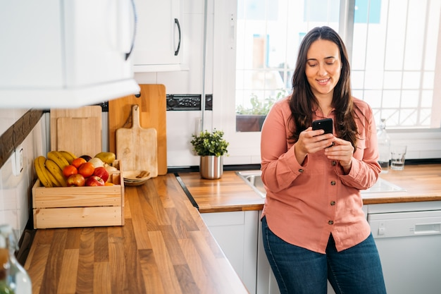 Messaggio di testo di battitura a macchina sorridente della giovane donna sullo smartphone nella sua cucina.
