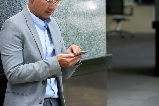 Messaggio di testo potato della lettura dell'uomo sul suo smartphone che sta all'edificio per uffici