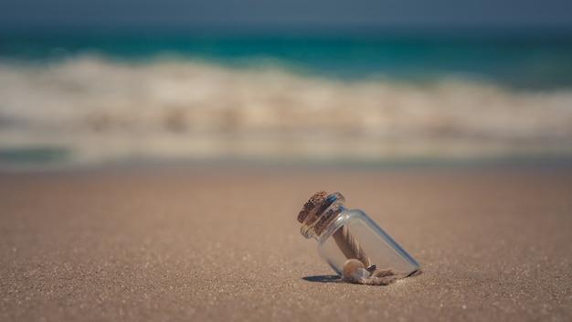 Messaggio in bottiglia sulla spiaggia di sabbia