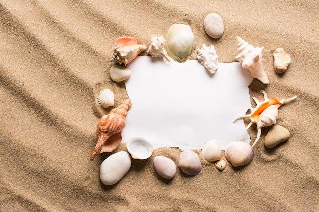 Messaggio in carta strappata sulla spiaggia. sfondo estate con sabbia calda