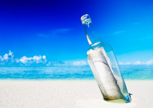 Messaggio in una bottiglia sulla spiaggia.
