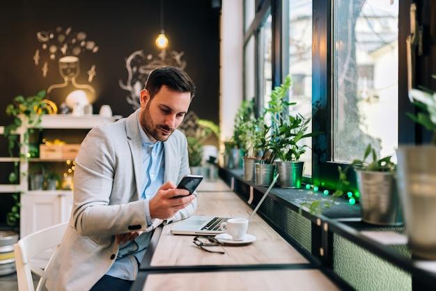 Messaggio serio della lettura dell'uomo d'affari su uno smartphone al caffè.
