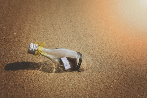 Messaggio sos in bottiglia di vetro sulla spiaggia.