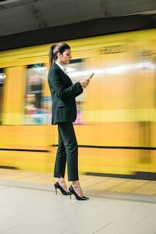 Messaggio texting alla moda della giovane donna di affari sul telefono cellulare che sta alla piattaforma