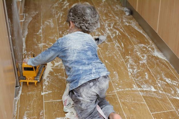 Messy cucina. piccolo bambino che gioca con farina al piano cucina.