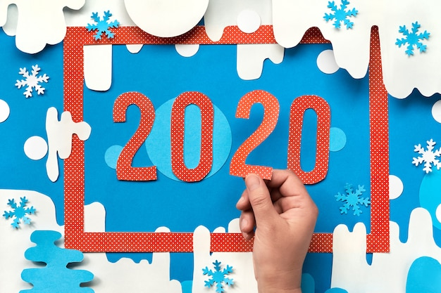Mestiere di carta, cornice rossa su sfondo invernale di carta con la mano che tiene il numero 2 nel numero 2020