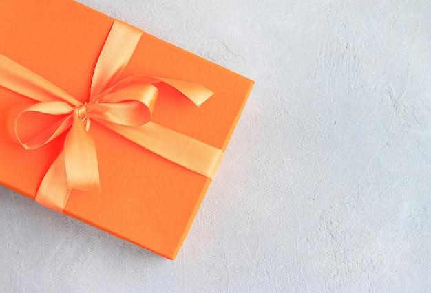 Mestiere il regalo di carta con il nastro arancio su fondo grigio con lo spazio della copia.