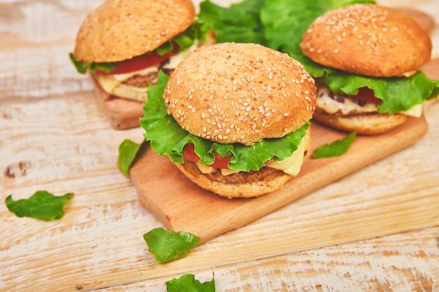 Mestiere l'hamburger di manzo sulla tavola di legno su fondo leggero