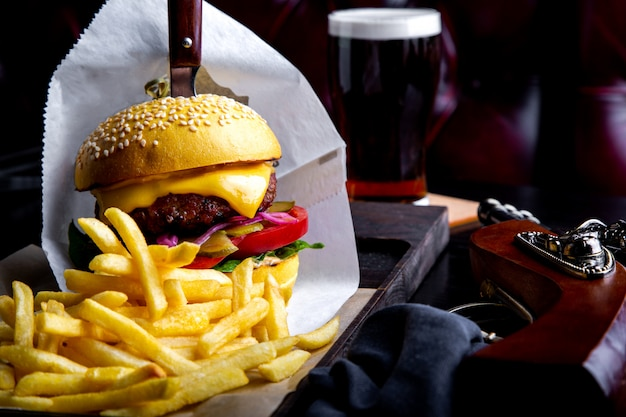 Mestiere l'hamburger e le patate fritte del manzo sulla tavola in ristorante con vetro di birra su oscurità. cornice per il pranzo moderna fast food