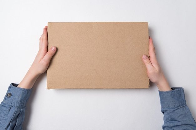 Mestiere la scatola di carta in mani dei bambini su fondo bianco. vista dall'alto. copia spazio.