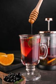 Mestolo di miele con un bicchiere di tè