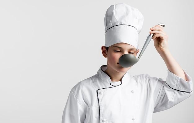 Mestolo di zuppa di degustazione giovane chef vista frontale
