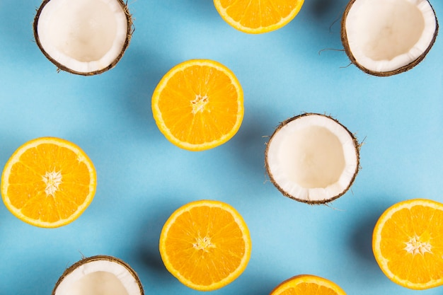Metà arancio mature succose e noce di cocco aperta bianca su un modello blu luminoso del fondo