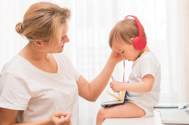 Metà colpo cute baby sulla scrivania con cuffie e madre