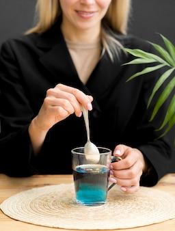 Metà colpo donna mescolando tè blu in vetro