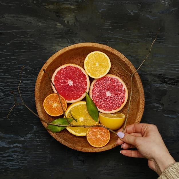 Metà degli agrumi del pompelmo sul piatto di legno