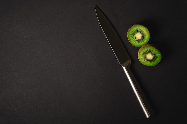 Metà dei kiwi affettata con il coltello da cucina, spazio della copia, vista superiore