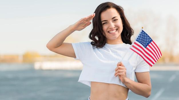 Metà della mano della donna del colpo che saluta e che tiene la bandiera degli sua