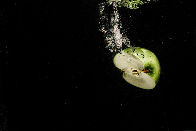 Metà della mela verde spruzza l'acqua mentre cade