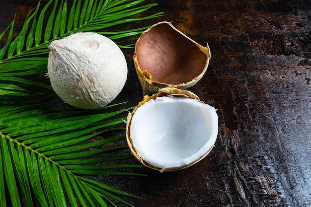 Metà della noce di cocco con foglie su fondo in legno
