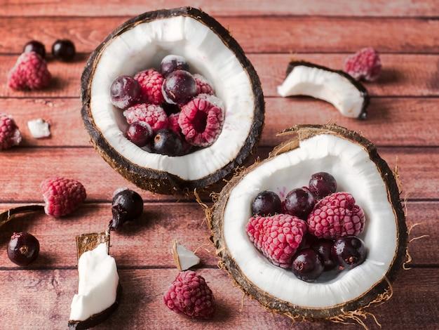 Metà della noce di cocco con le bacche congelate su un fondo di legno scuro