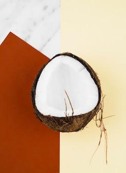 Metà della noce di cocco matura sul rosso; sfondo bianco e giallo