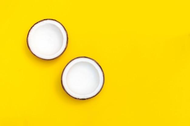 Metà della noce di cocco su fondo giallo luminoso