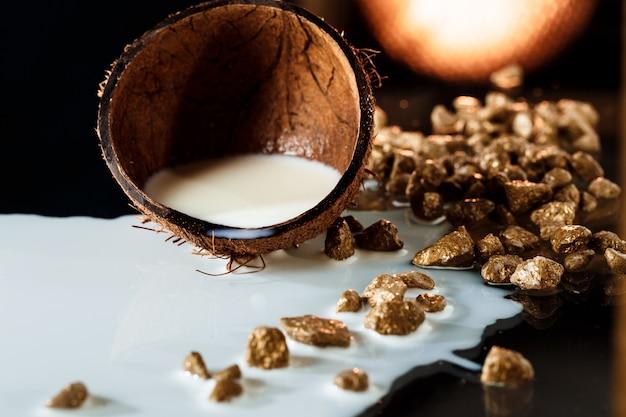 Metà di cocco con latte sulla superficie nera