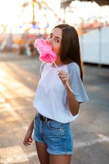 Metà di colpo donna che mangia zucchero filato rosa