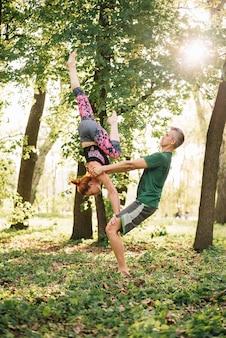 Metà di coppie adulte adatte che fanno l'equilibrio di acroyoga in natura