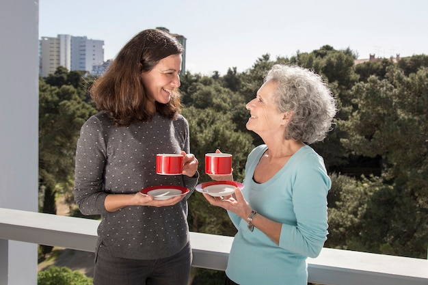 Metà di donna adulta che beve il tè con la sua madre senior sul balcone