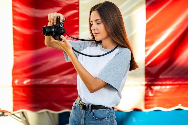 Metà di donna del colpo che prende foto con la macchina fotografica