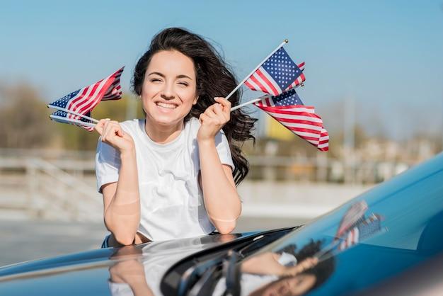 Metà di donna del colpo che tiene le bandiere degli sua sull'automobile