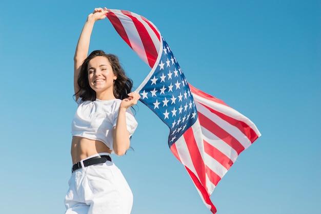 Metà di giovane donna del colpo che tiene la grande bandiera e sorridere degli sua