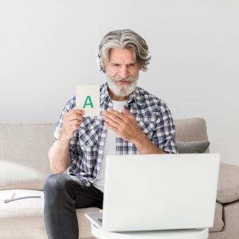 Metà di insegnante del colpo che mostra la carta di lettera al computer portatile