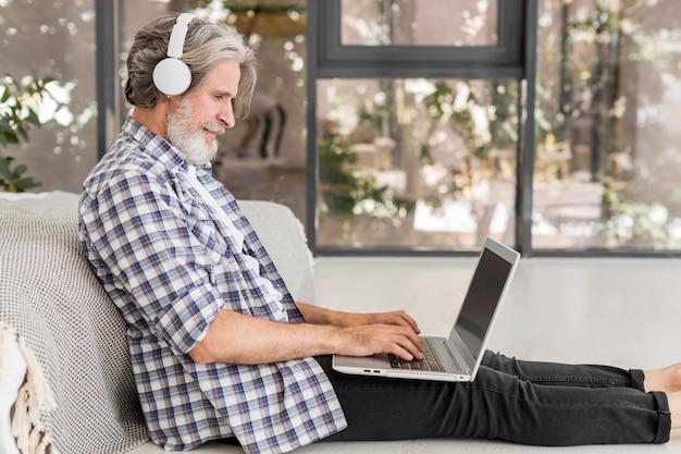 Metà di insegnante del colpo che per mezzo del computer portatile che si siede sul pavimento