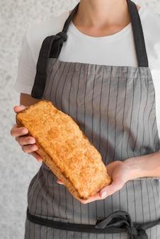 Metà di pane di banana della tenuta della donna del colpo