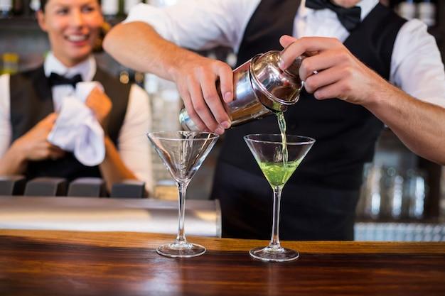 Metà di sezione del barista che versa cocktail nei bicchieri