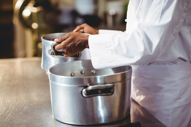 Metà di sezione del cuoco unico che tiene pentola di cottura
