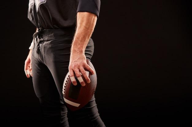 Metà di sezione del giocatore di football americano con la palla contro il nero, spazio della copia, vista laterale