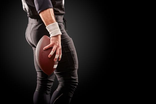 Metà di sezione del giocatore di football americano con la palla contro il nero, spazio della copia, vista posteriore