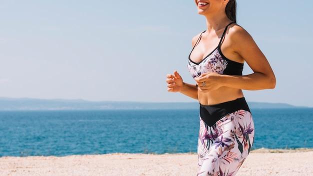 Metà di sezione del giovane pareggiatore femminile di forma fisica che corre vicino alla spiaggia