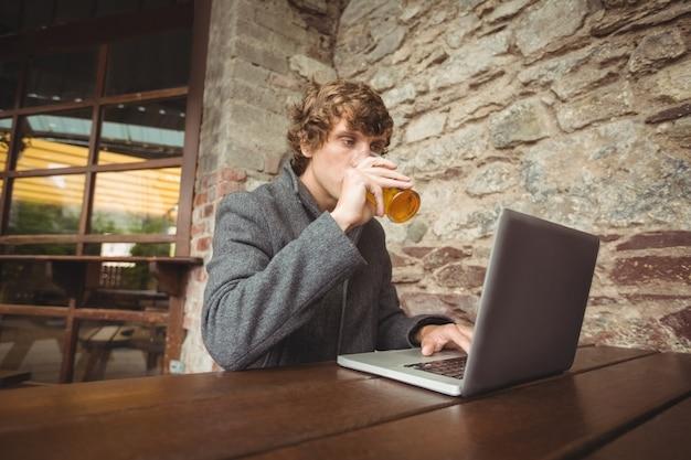 Metà di sezione dell'uomo che tiene vetro di birra e che per mezzo del computer portatile