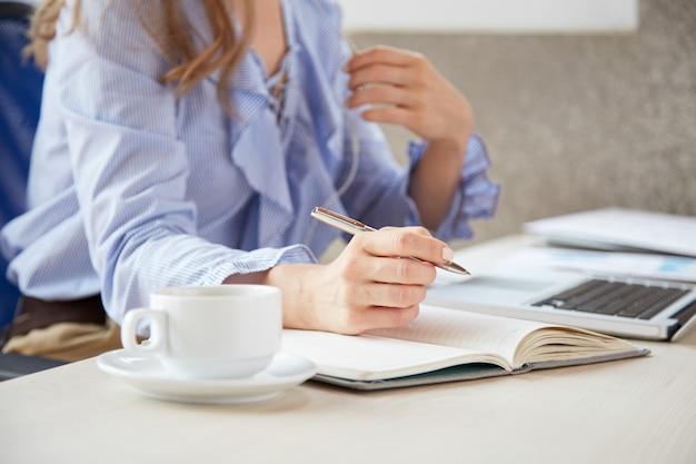 Metà di sezione della donna anonima che fa le note che si siedono allo scrittorio